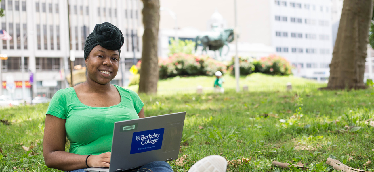 Female student on laptop sitting outside