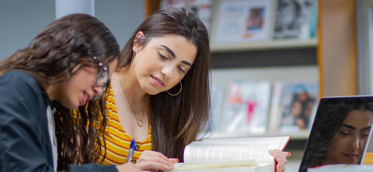 Two female students studying together in a library.
