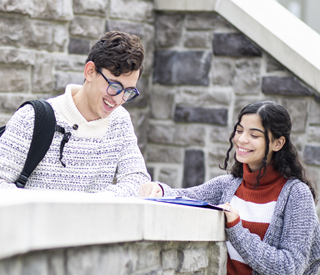 Male and female student reading a book on a ledge at the Woodland Park Campus mobile image
