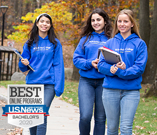 Three female students walking outside Berkeley College Woodland Park campus in fall wearing Berkeley College Your Potential is Our Promise sweatshirts holding books in their hands with US News and World Report Best for Online Program Bachelors 2020 badge image on lefthand side.  mobile image