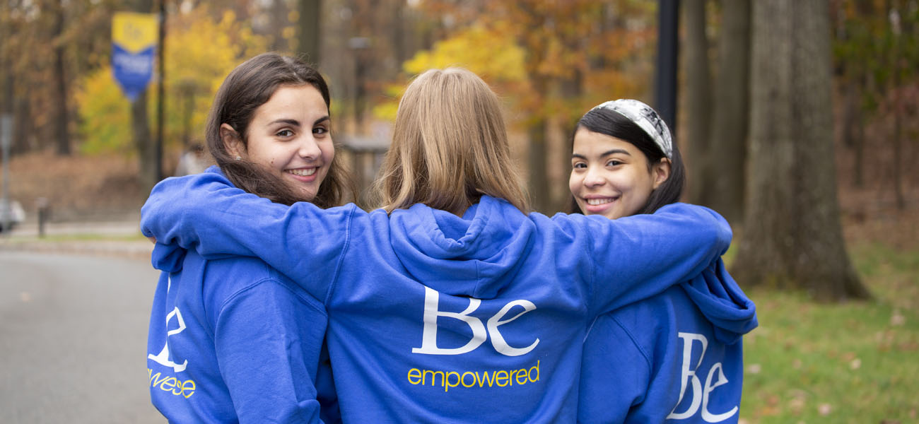 Three female students with Be sweatshirts with their arms around each other
