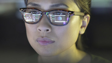 Female student with reflection of computer in her glasses