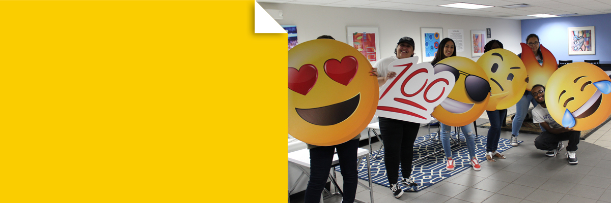Students with emoji cut outs at New Student Orientation