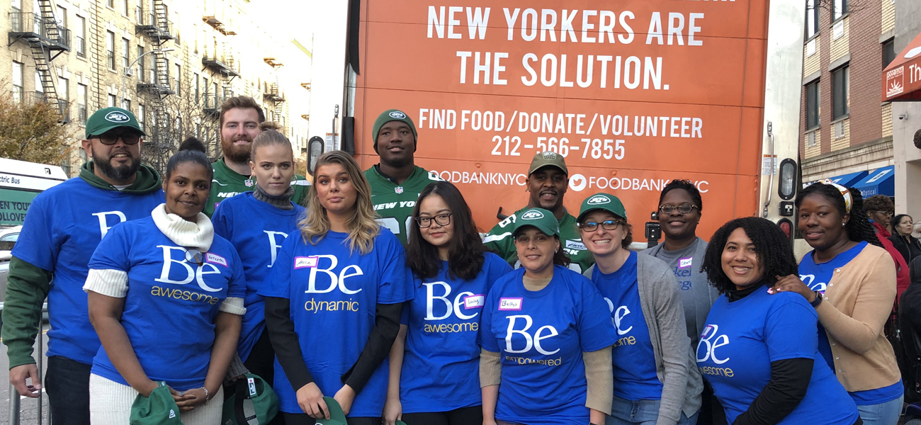 Group of Berkeley staff and students with players from the NY Jets in front of Food Bank of NY truck