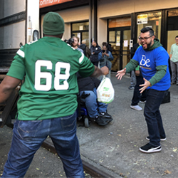 Jets player throwing turkey to Berkeley associate