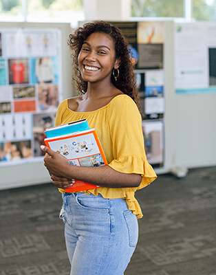 Gleny Bravo smiling carrying her books
