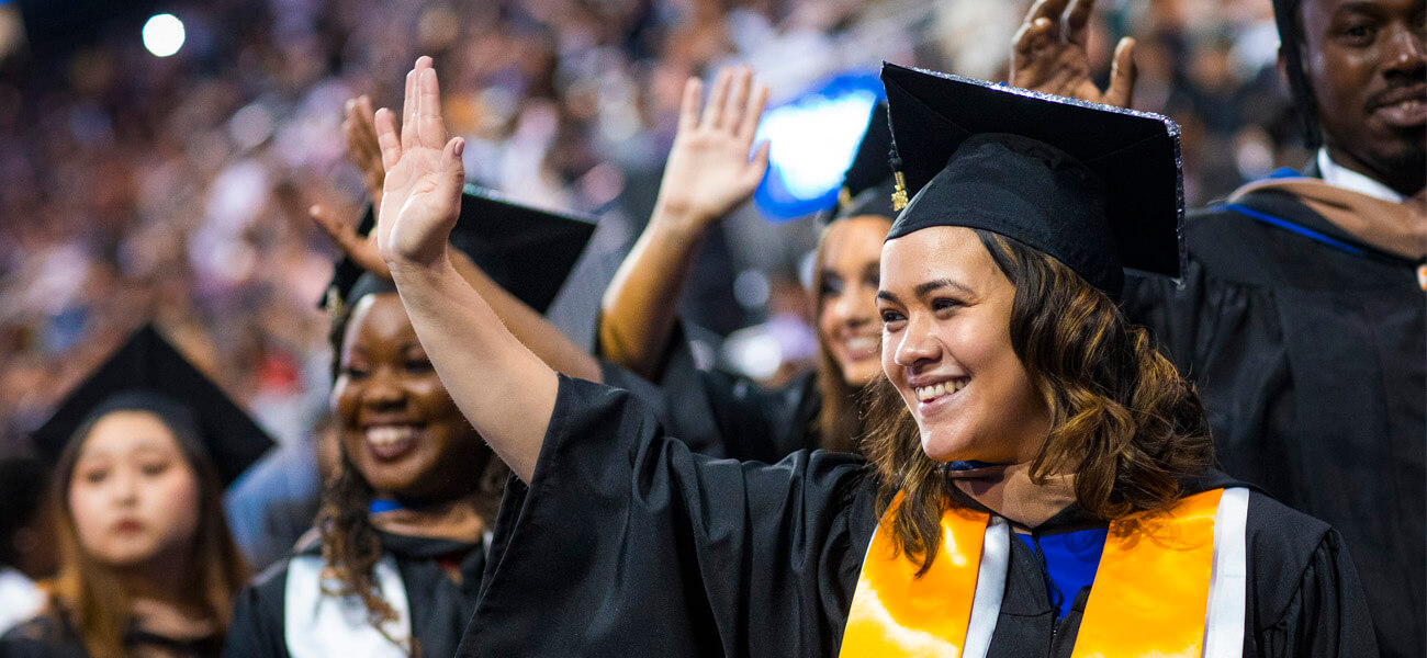 Female student in cap and down at Commencement waving