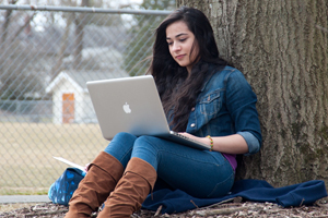 Photo of female student working on her laptop outdoors.
