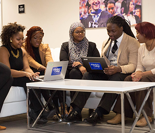 Group of 7 students sitting on couch looking at laptop mobile image