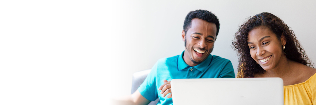 Image of 2 online students smiling while working in front of a laptop