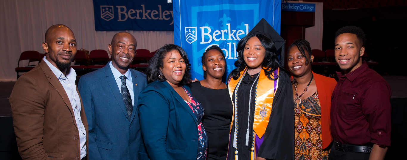 Photo of Berkeley College graduate at Commencement with family.