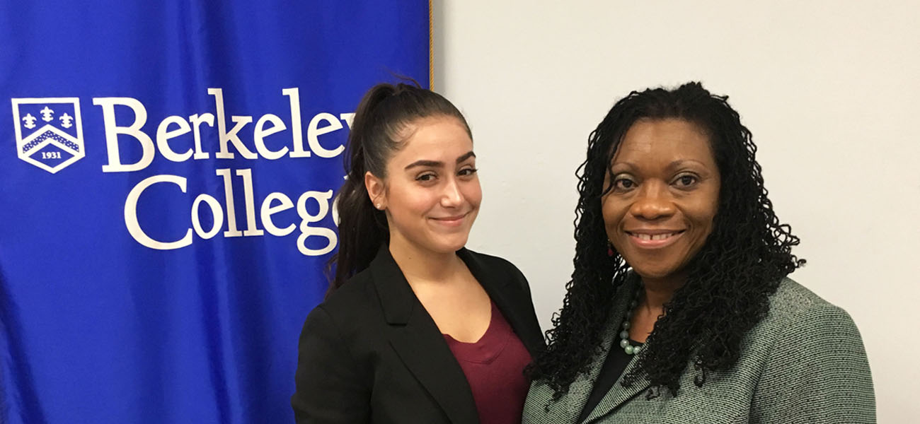 Moya Bansile with female student in front of Berkeley College Banner