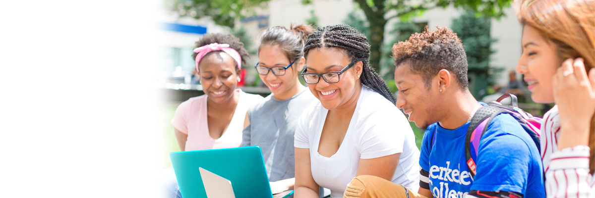 Photo of Berkeley College students on a laptop outdoors.