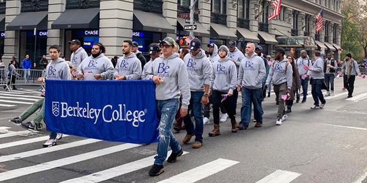 Berkeley College group walking with Berkeley College banner in gray Be Successful sweatshirts in NYC