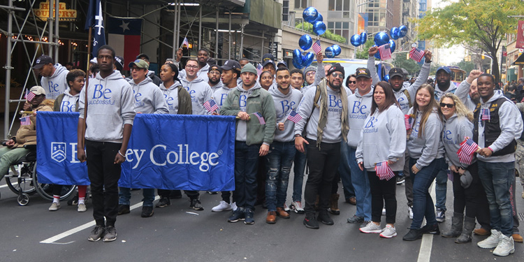 Group of Berkeley students at Veterans Day Parade in NYC holding Berkeley College flag