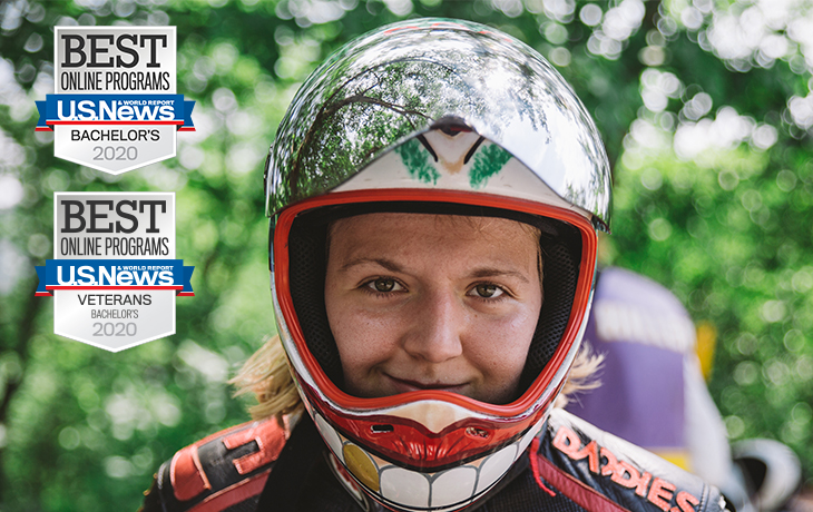 Emily Pross in racing helmet with US News Badges